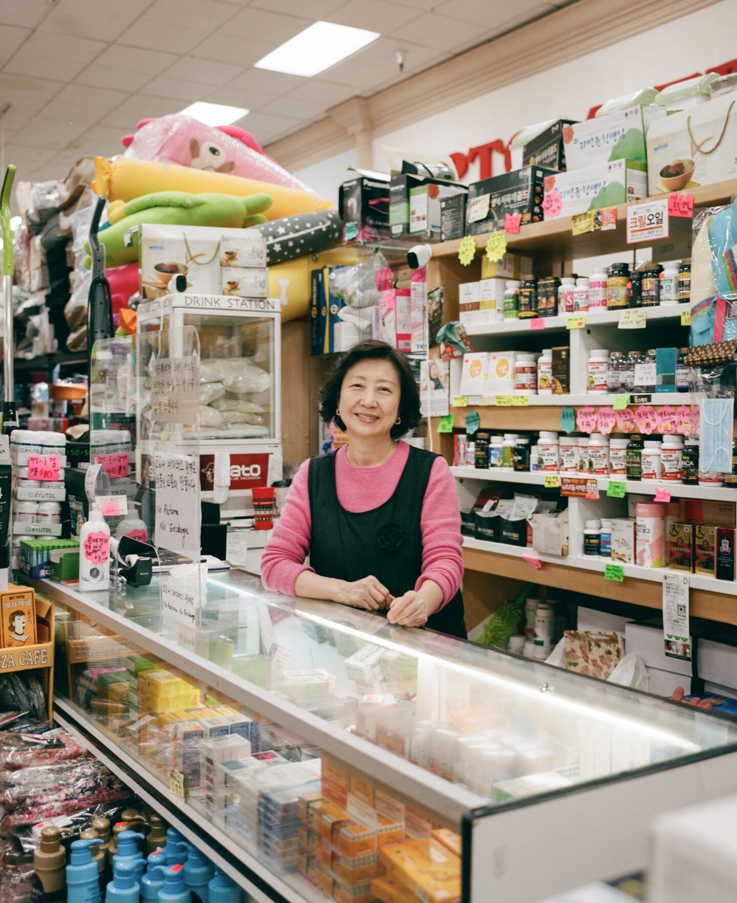 A shopkeeper in Koreatown stands by the checkout counter smiling with rows of goods behind her.