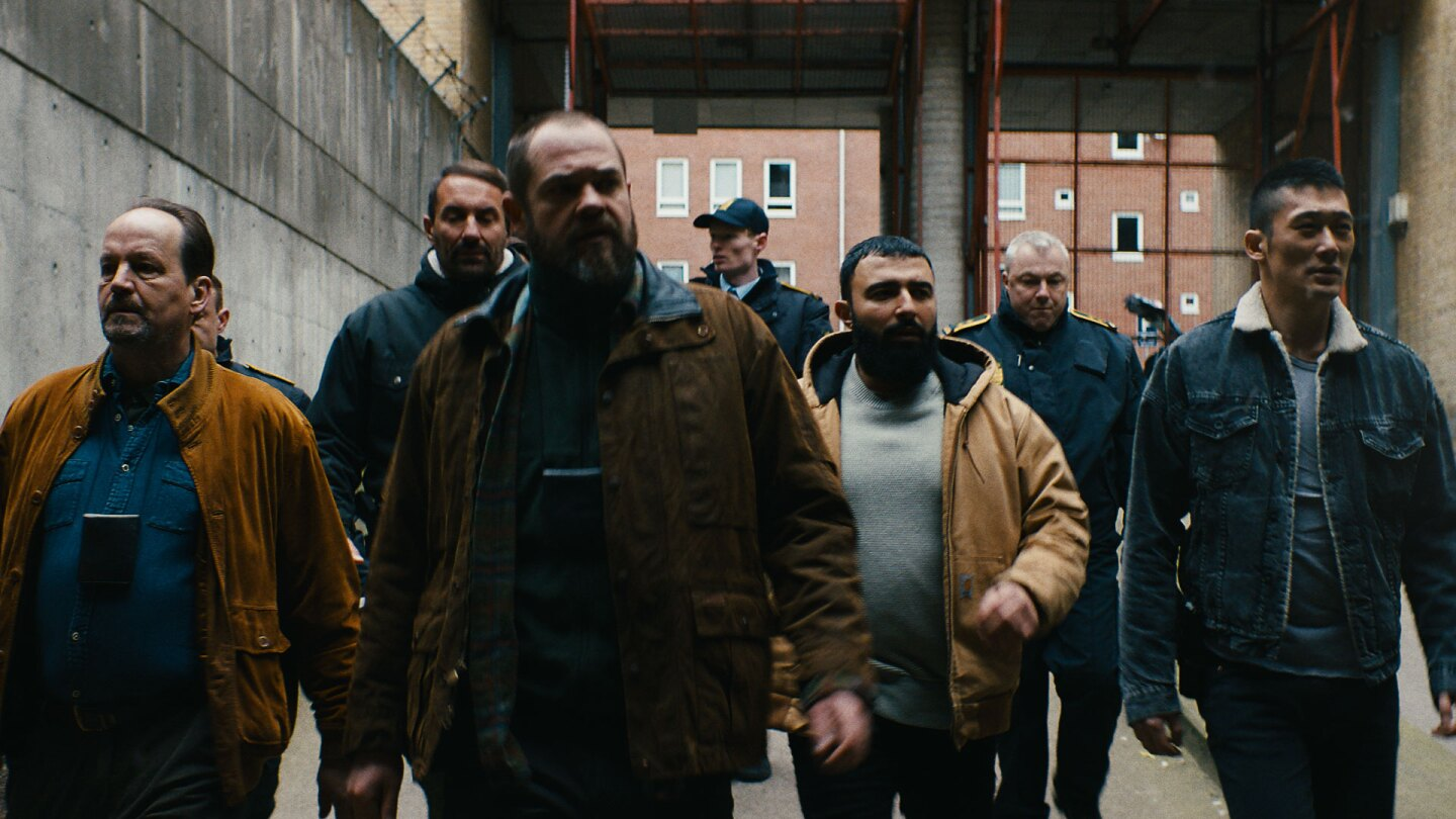"Group of men walk through industrial area. | Laust Trier Moerk / ""Follow the Money"""