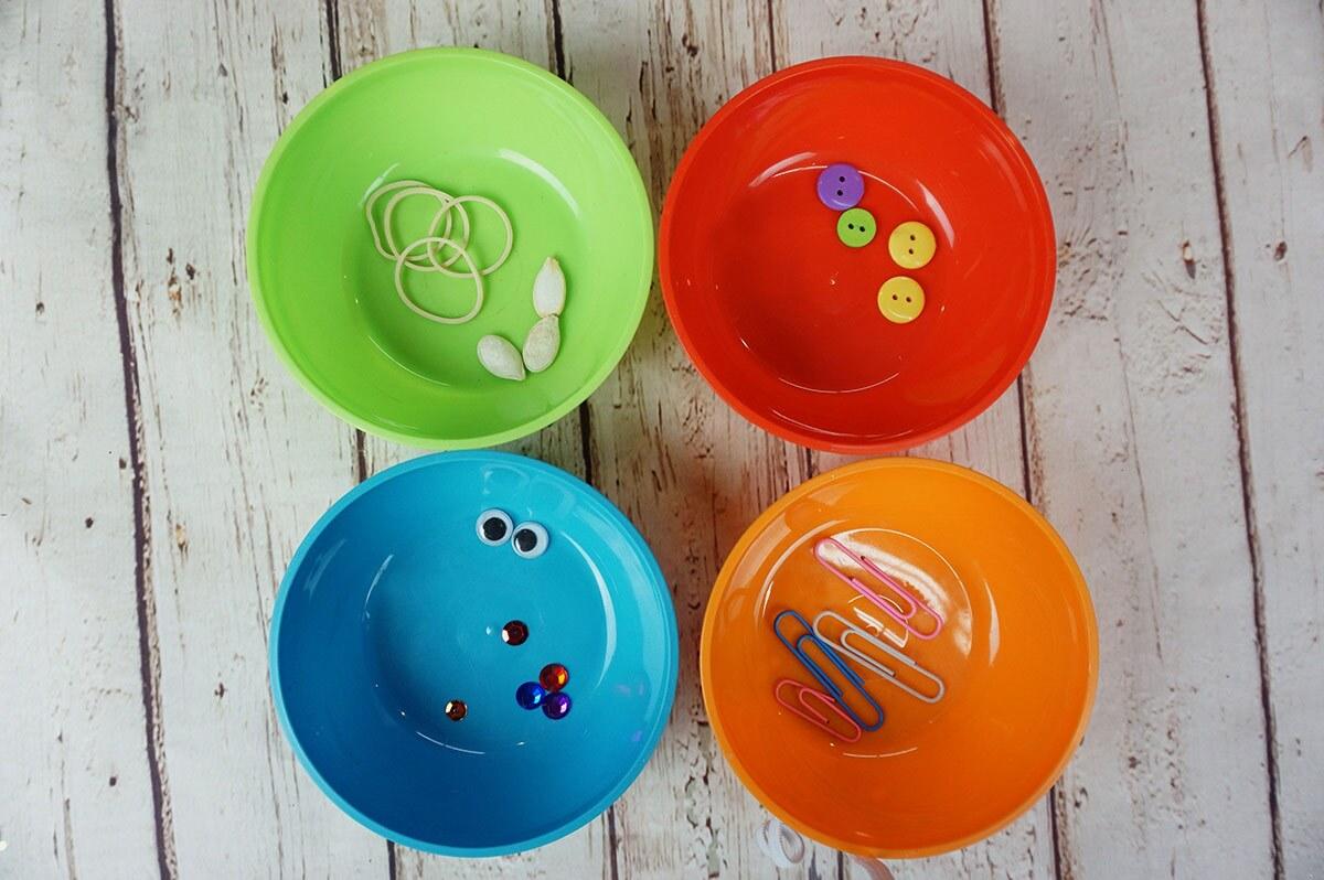 Cuatro tazones de colores llenos de artículos ordenados por tipo, incluyendo ligas, semillas, clips de papel, botones y lentejuelas.