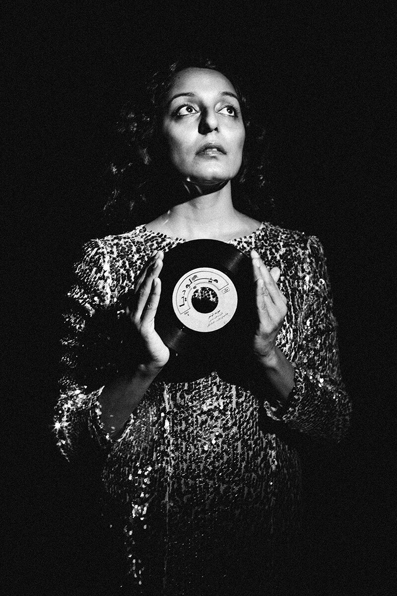 Black and white photo of a woman standing holding a vinyl record