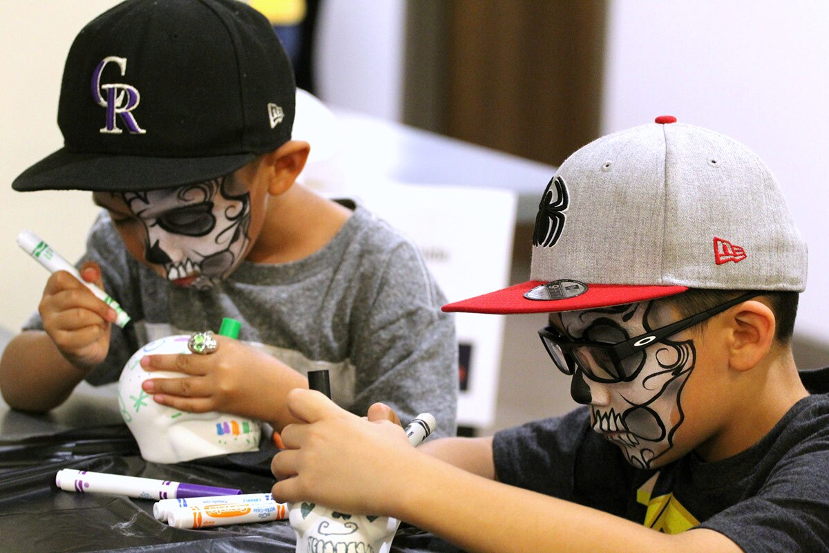 Two young boys wear skull face paint as they decorate small white plastic skulls for Day of the Dead.