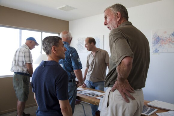 Bernard Leibov (left) talking with local sculptor, Steve Rieman (right) at BoxoHouse. May 2012 resident artist, Tim Saternow is at back behind table in middle.    Photo: Kim Stringfellow.