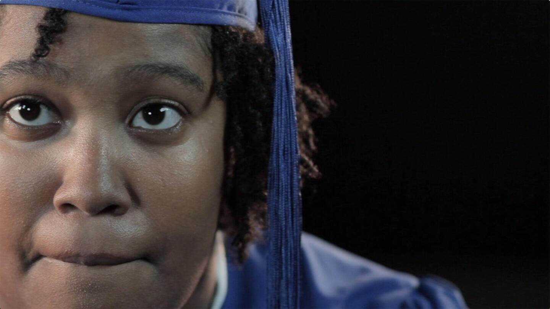 Closeup of a student wearing graduation garb biting their lip.