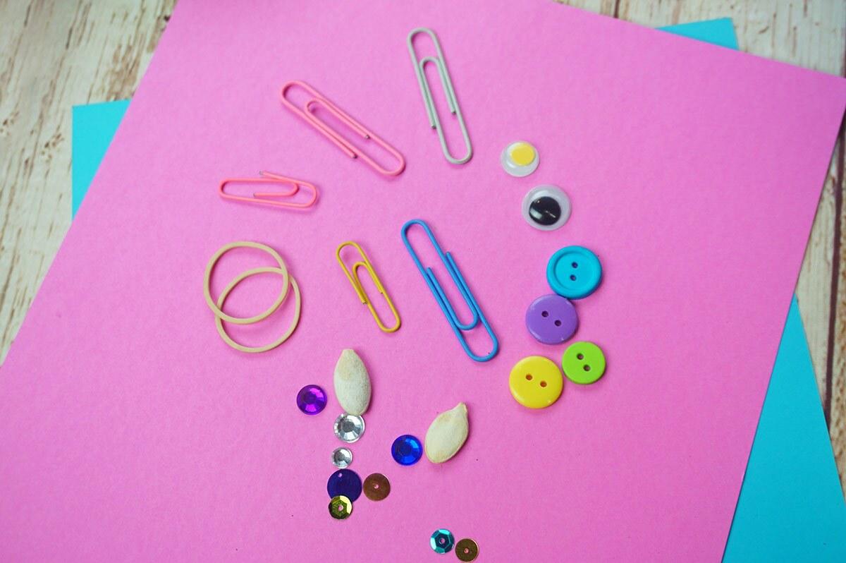 Una hoja de papel rosa cubierta con una variedad de artículos pequeños que incluyen ojos saltones, ligas, clips de papel, botones, semillas y lentejuelas.