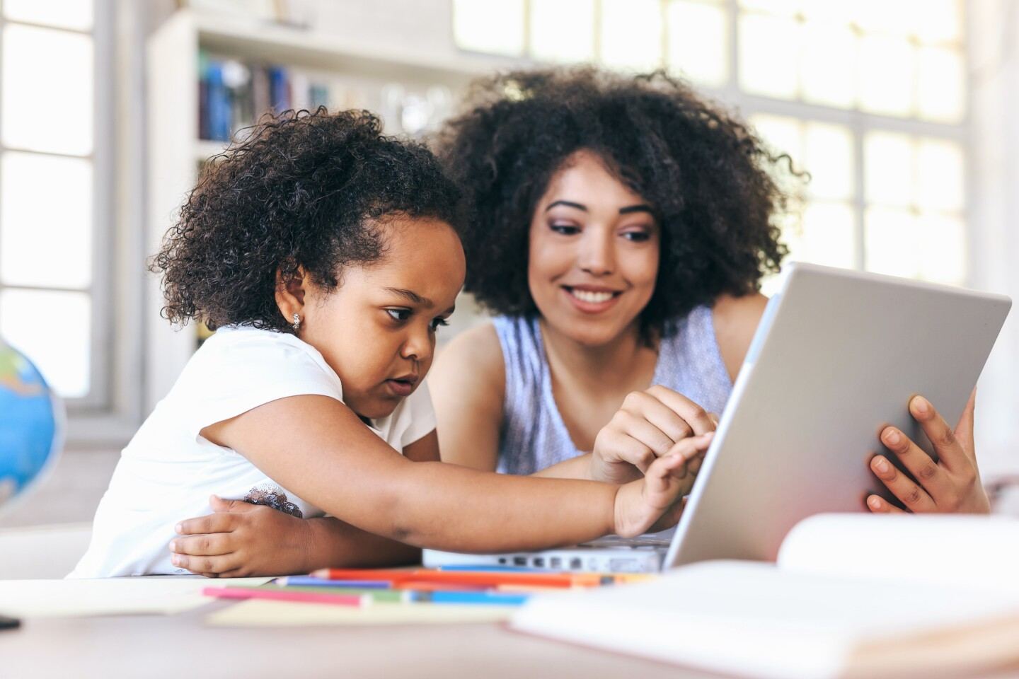 A young mother and child work on a computer together. iStock