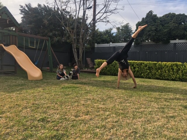 Kathleen Abing doing cartwheels outdoors.