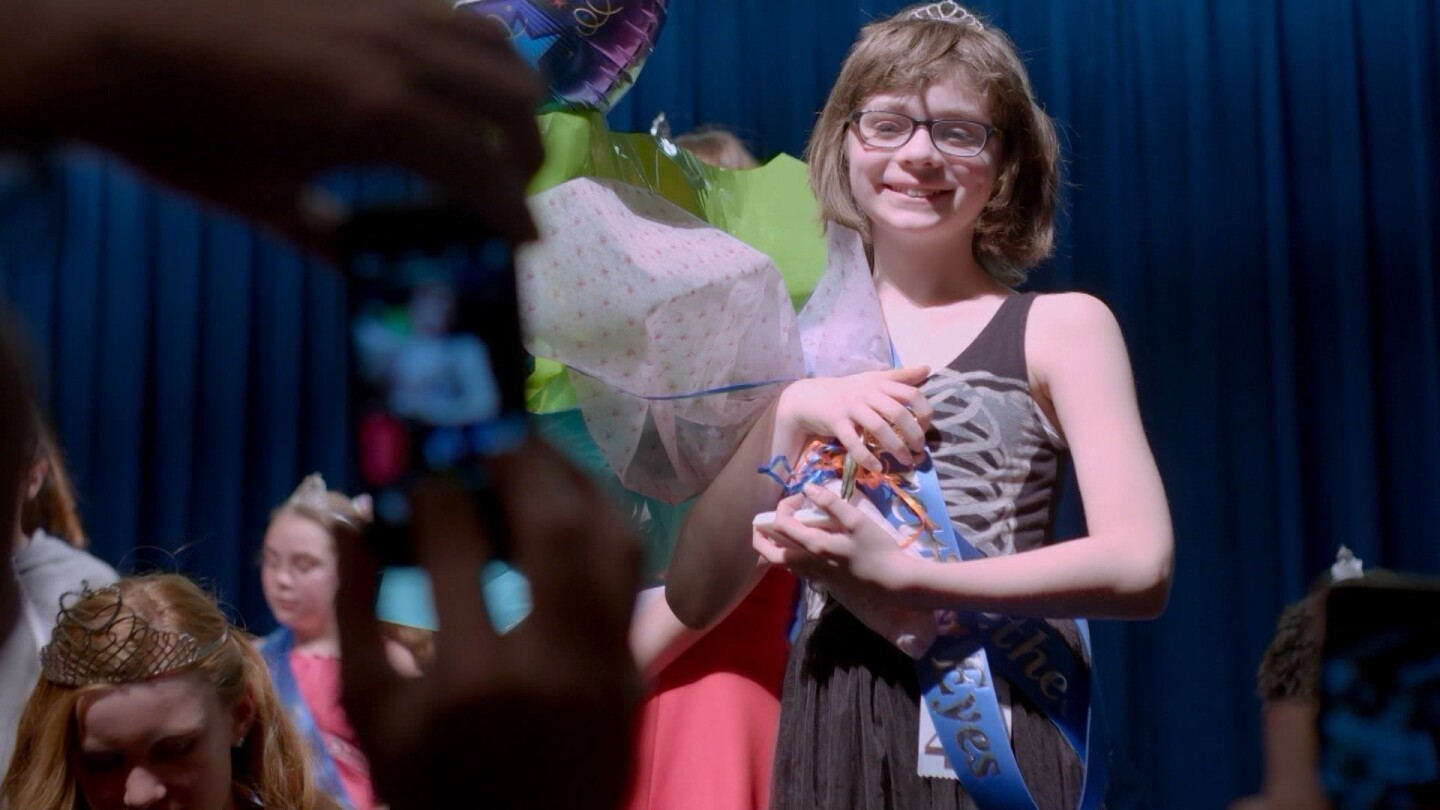 """Ren McCarthy holds a bouquet of flowers and smiles on a stage. 
