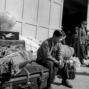 """Mitsunobu """"Mits"""" Kojimoto, 19, arrives with his personal belongings to be forcibly removed from San Francisco to the Santa Anita Assembly Center in Arcadia, Calif.   Dorothea Lange, War Relocation Authority Photographs"""