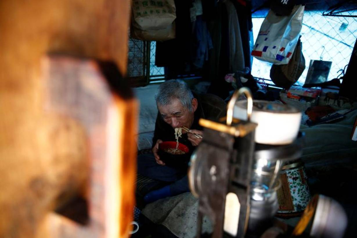 RCHIVE PHOTO: Homeless Makoto Shinbo eats his lunch at his makeshift house at Miyashita park in Tokyo, Japan, February 17, 2017. Picture taken on February 17, 2017. | REUTERS/Kim Kyung-Hoon