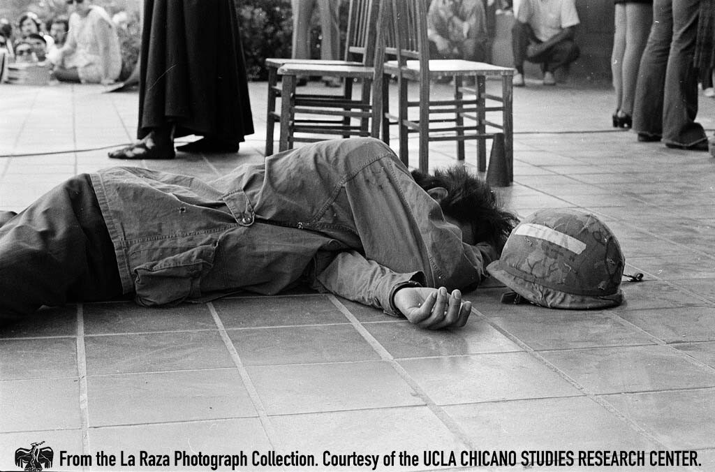 CSRC_LaRaza_B5F3C3_PA_010 Person lying on stage during a performance at Fresno Moratorium | Pedro Arias, La Raza photograph collection. Courtesy of UCLA Chicano Studies Research Center