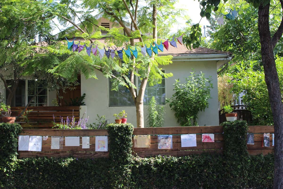 Dan Fields' Los Feliz fence gallery features children's artwork hanging from a cable.