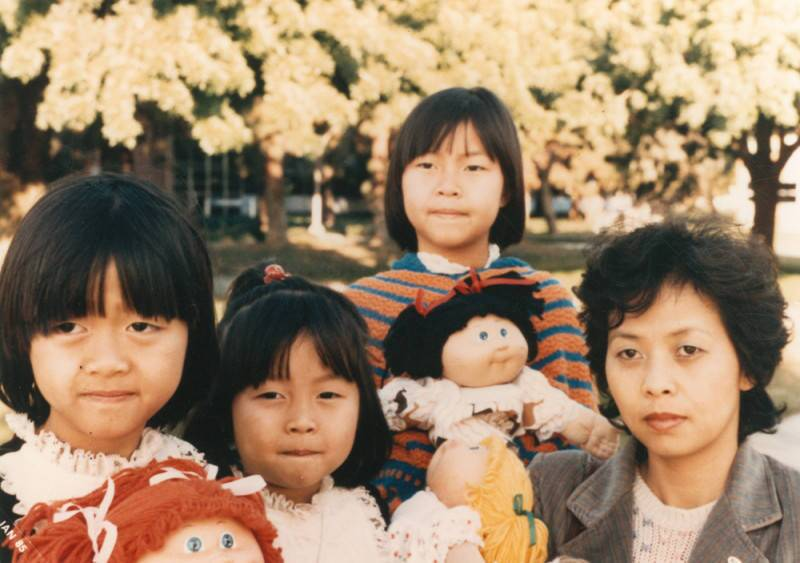 A Vietnamese American mother and her daughters pose for the camera in front of a tree with yellow flowers.