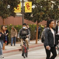People walking and bike riding on USC campus on March 9, 2020 | Al Seib/Los Angeles Times/Getty Images