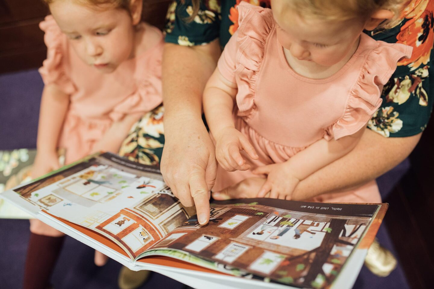 A woman reads over two little girls' shoulders who are wearing matching pink dresses as they hold a picture book.