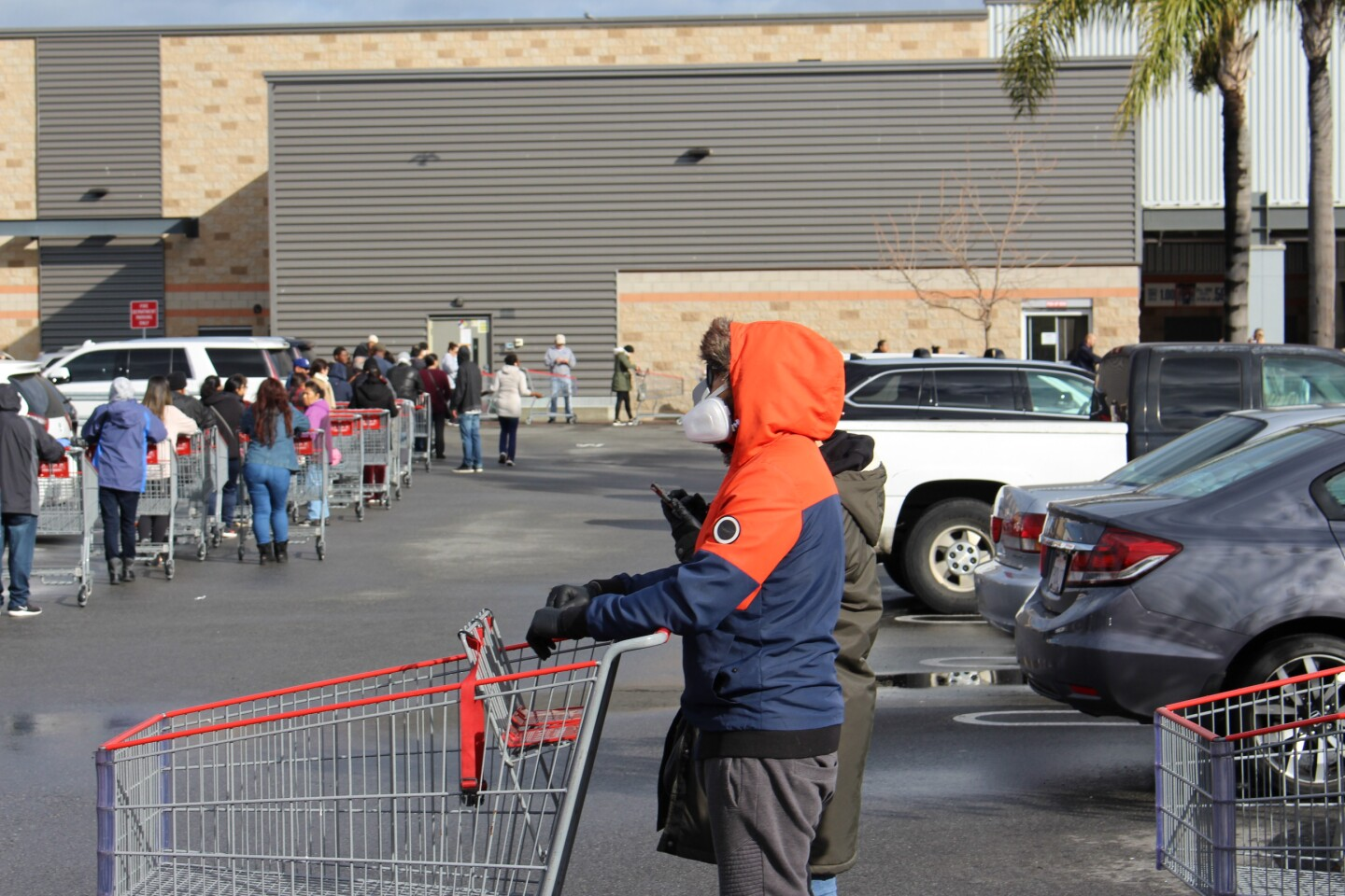 Man in orange sweatshirt with mask with a shopping cart, outside of Costco on March 15th, 2020