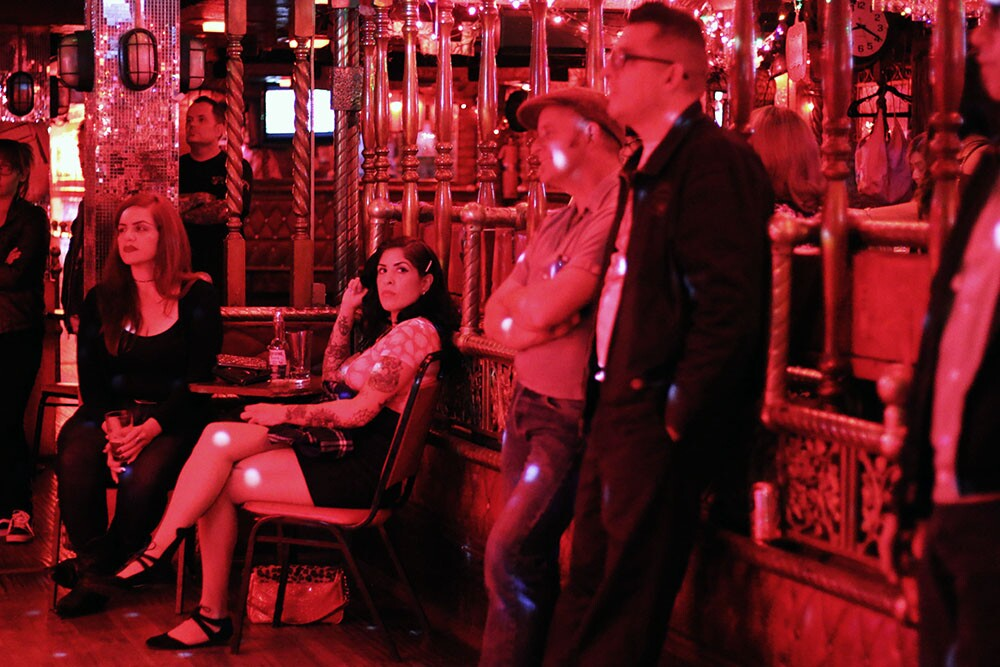 People sit and stand around the dance floor under a red light.