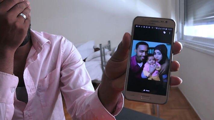 Muaz Mahmud Ayimoo shows photograph of his family