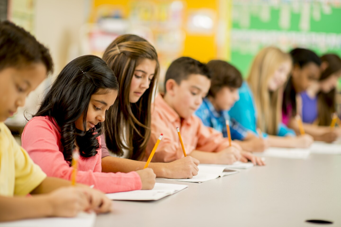 A row of students taking a test. | iStock
