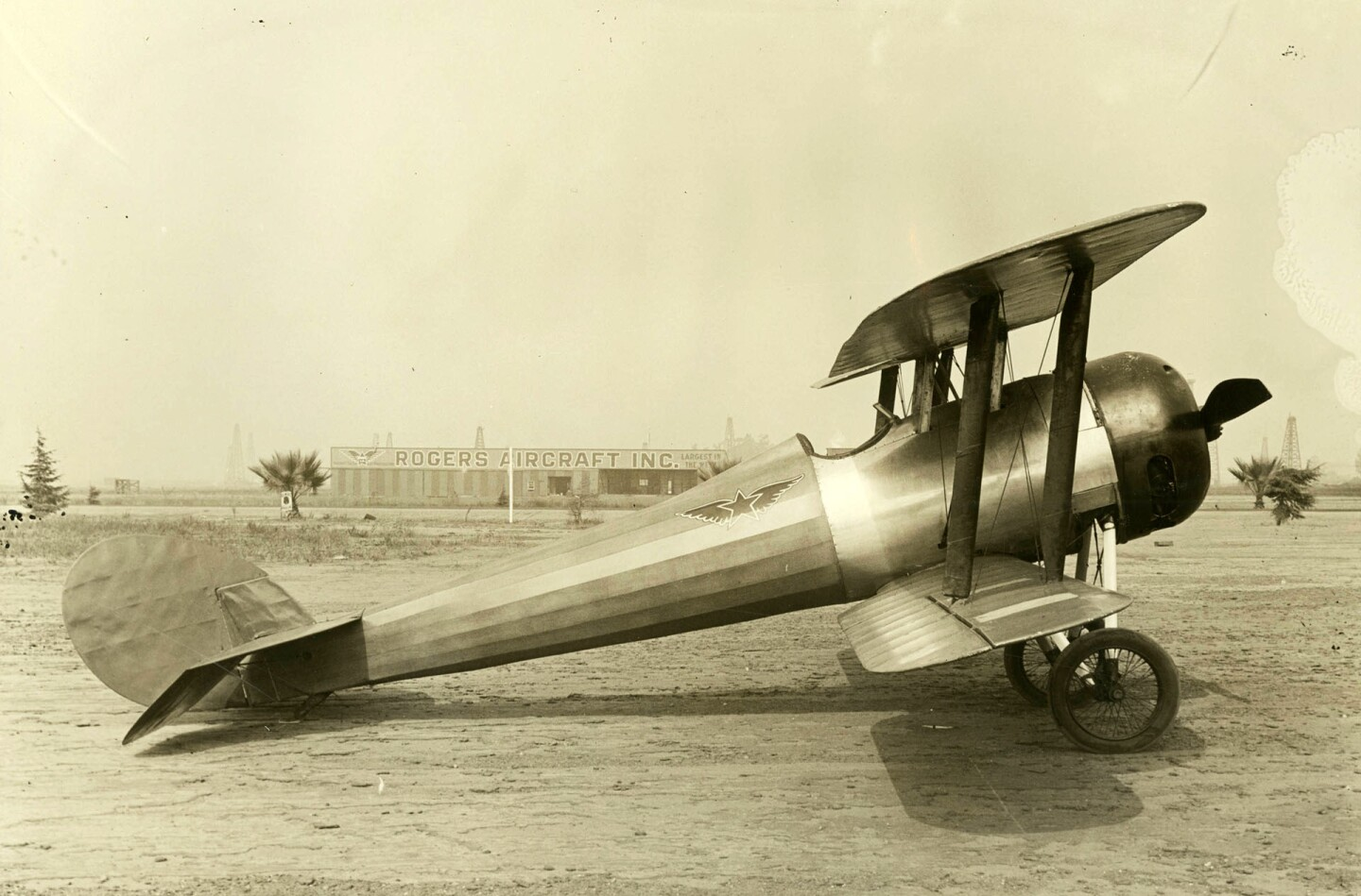 Airplane parked at Rogers Airport with Rogers Aircraft Incorporated building in the background, ca.1922
