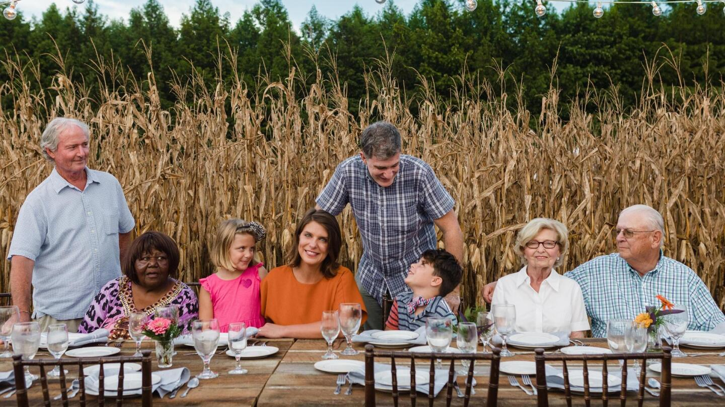 A family gathers at a dining table outdoors.