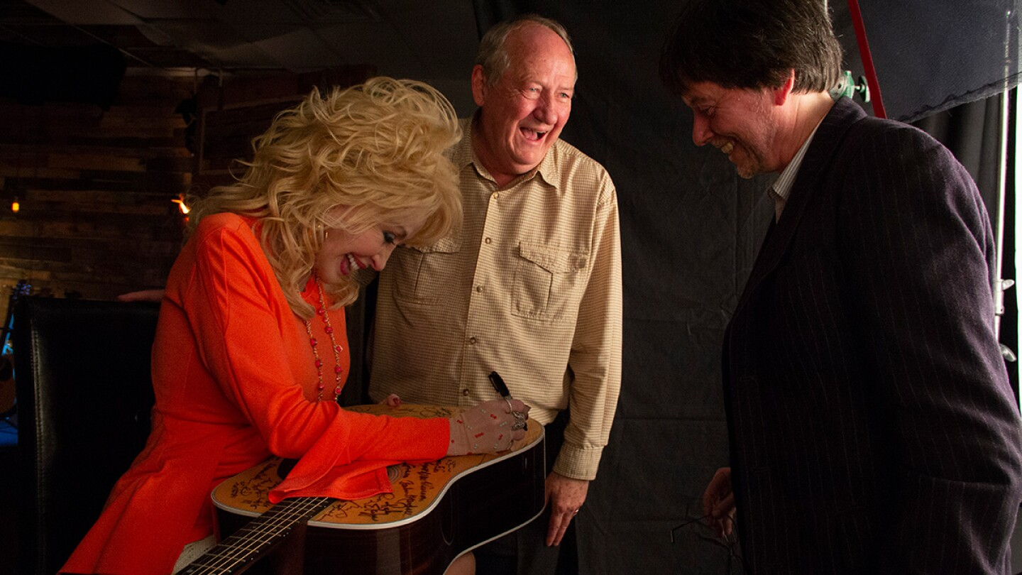 Dolly Parton signs Martin D-28 guitar. Parton is among the 76 of the 101 country music artists interviewed for the series who signed two Martin D-28 guitars. | Courtesy of Katy Haas
