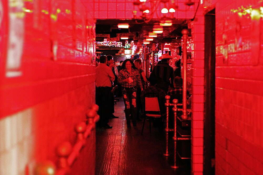 A woman walks toward a hallway under red lights.
