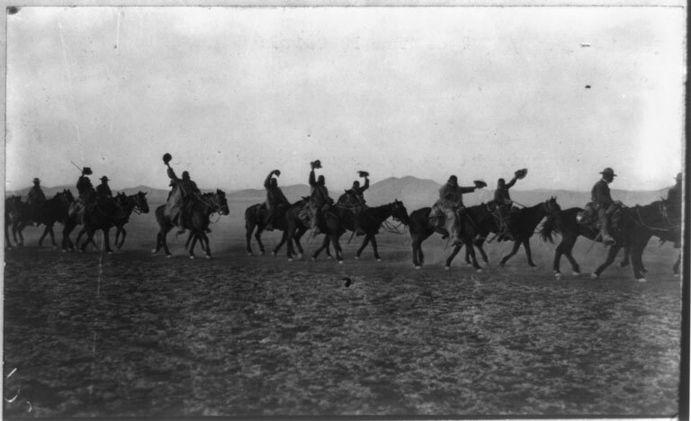 Members of the 10th Cavalry (African American) waving hats as they ride on a U.S. campaign against Pancho Villa at the Mexican border. (1916) | Library of Congress