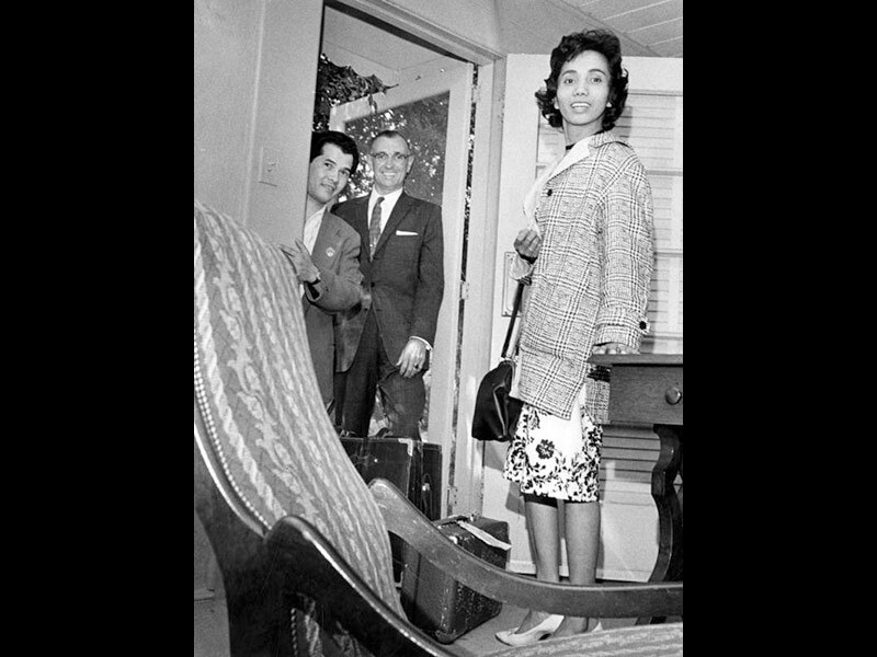 Black and white photo of two men standing in a doorway and a woman standing inside a room, smiling