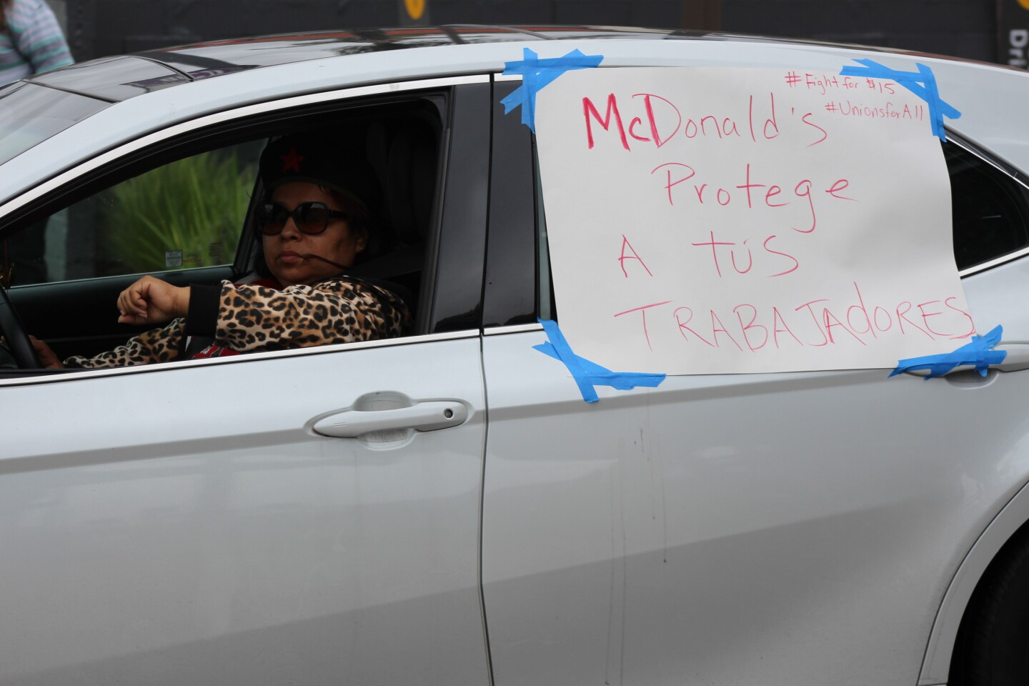 "Sign reading ""McDonalds protege a tús trabajadores #Fightfor15""on car window, with woman in driver's seat during McDonald's protest on April 6, 2020 