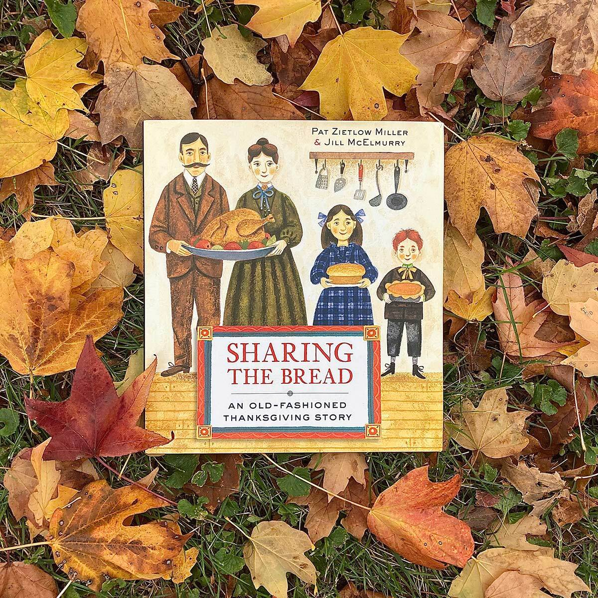 """""""Sharing the Bread: An Old Fashioned Thanksgiving Story"""" written by Pat Zietlow Miller and illustrated by Jill McElmurry book cover featuring an illustration of a family holding dishes of food. The book is sitting on top of fall leaves."""