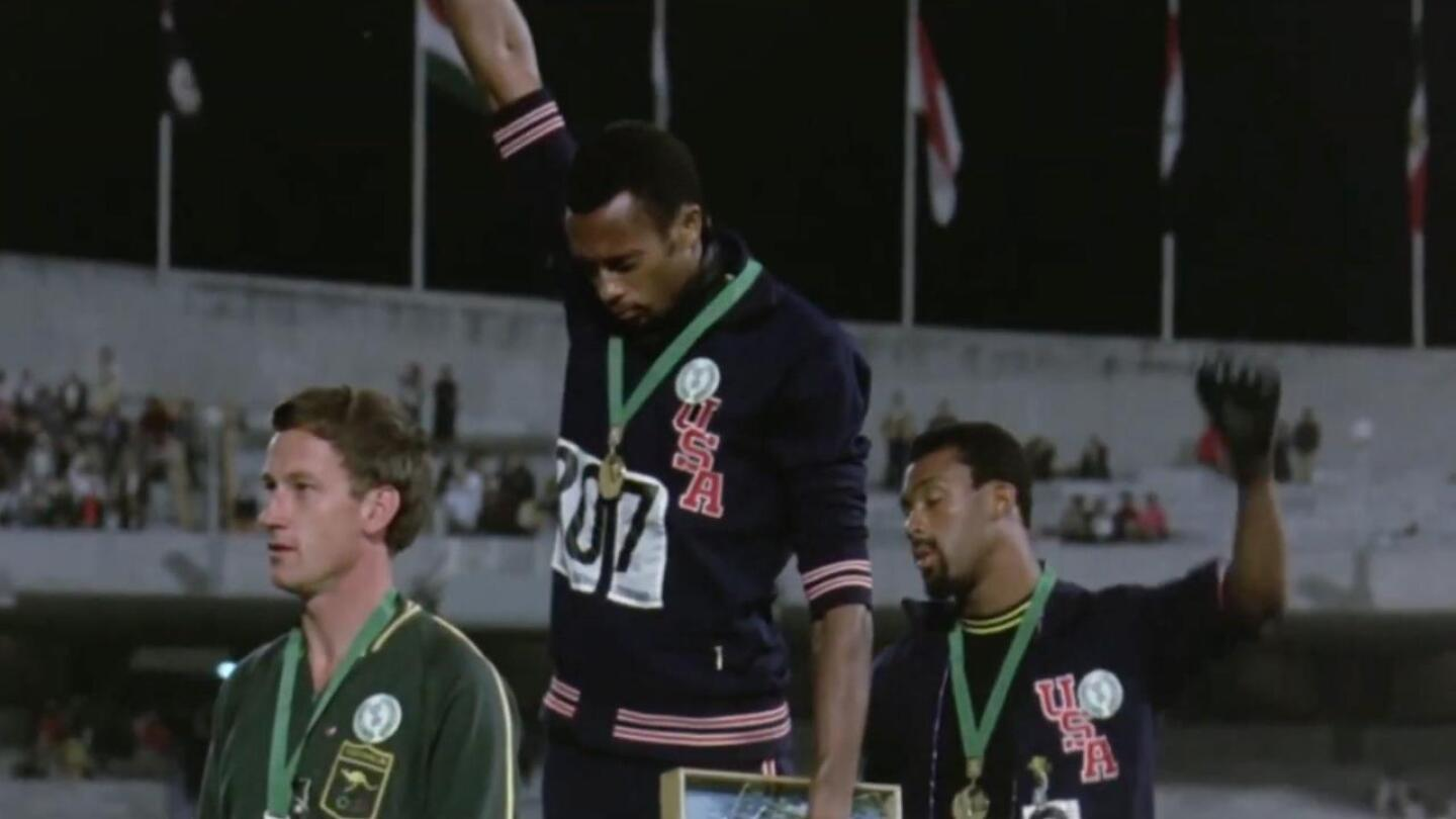 Tommie Smith and John Carlos doing the Black Power salute at a podium at the 1968 Summer Olympics.
