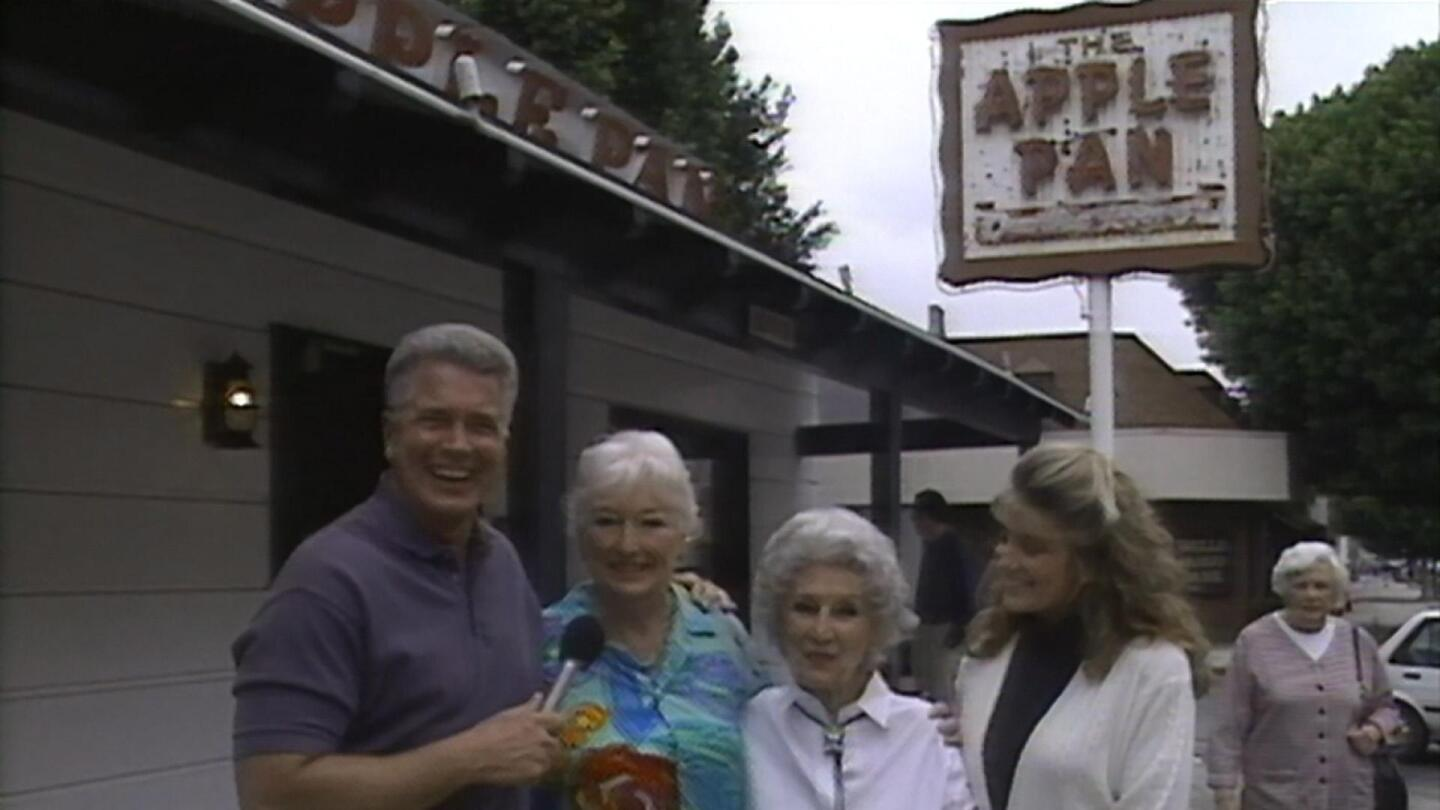 """Huell stands outside a building called """"The Apple Pan"""" with a few others."""