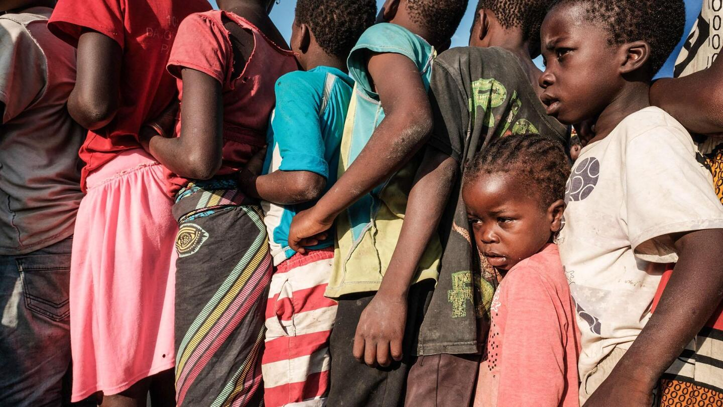 African children line up in a tight line, as two younger children wedged in the line looks on.