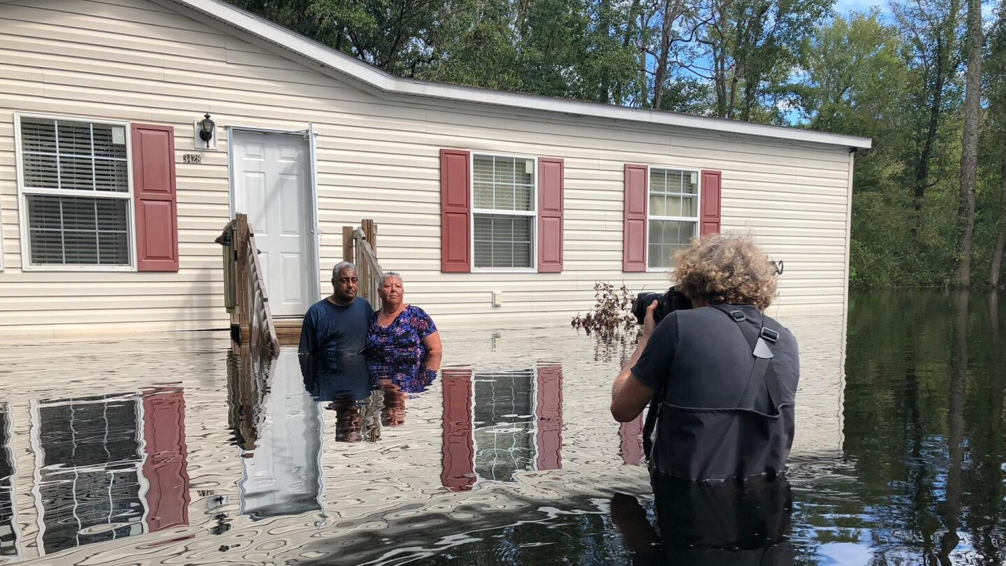 "A couple standing in a body of flood water up to their waists poses in front of their home as a photographer takes their picture. | ""H20: The Molecule That Made Us - Crisis"""