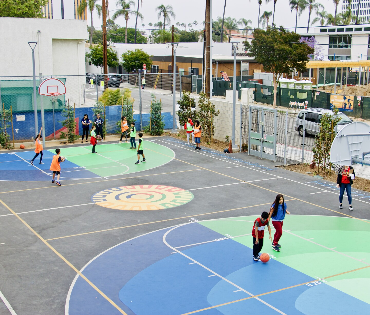 Children play a fraction game on a basketball court.