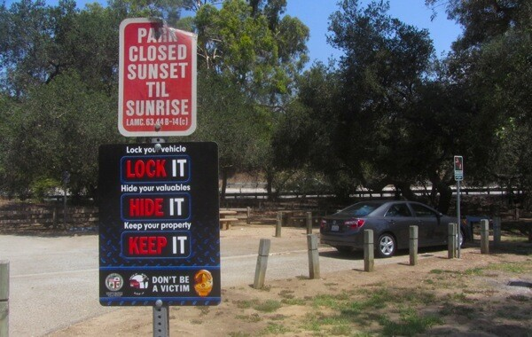 A sign advising visitors of best practices at the entrance of a Griffith Park parking lot.   Photo: Zach Behrens/KCET