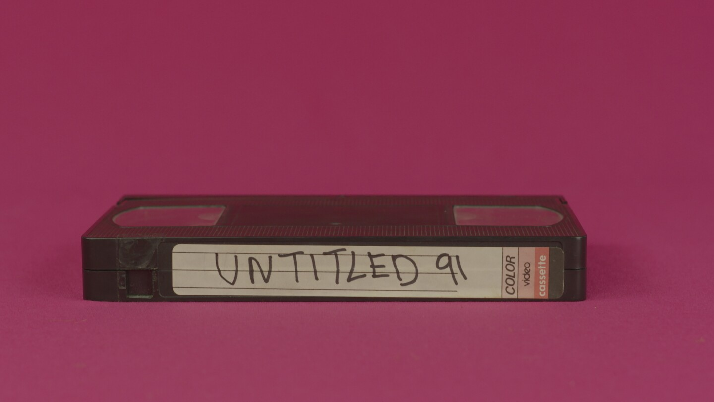 "Hector Gachan music video still: a VHS tape on a fuschia background. Tape reads ""Untitled 91,"" which is the name of the song."