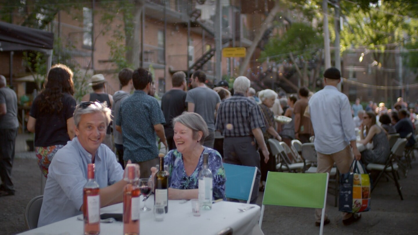 "Mikael Coville-Andersen sits with a woman at a table and smiles at the camera, while a large gathering of people stand and sit at tables behind them. | From ""Life-Sized City: Montreal"""