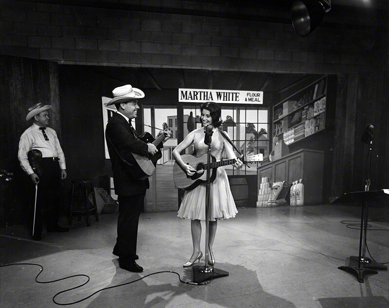 Earl Scruggs and June Carter on the set of the Flatt & Scruggs Grand Ole Opry Show, 1961. Paul Warren (in background), fiddler, Foggy Mountain Boys. © Les Leverett