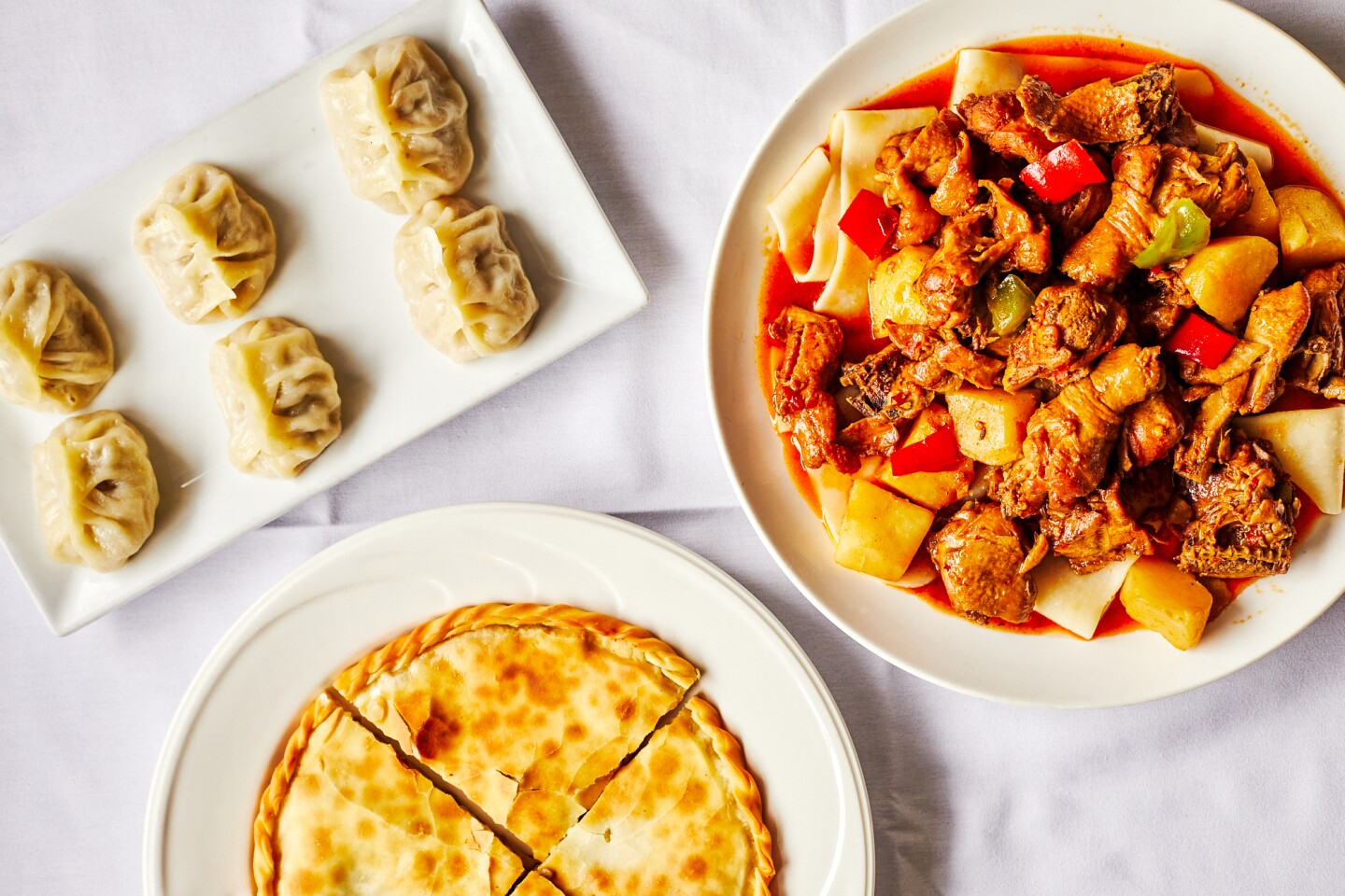Three dishes served Dolan's in Alhambra are goshnaan, a meat pie; manta, a steamed dumpling and big plate chicken, a kind of chicken stew served noodles.