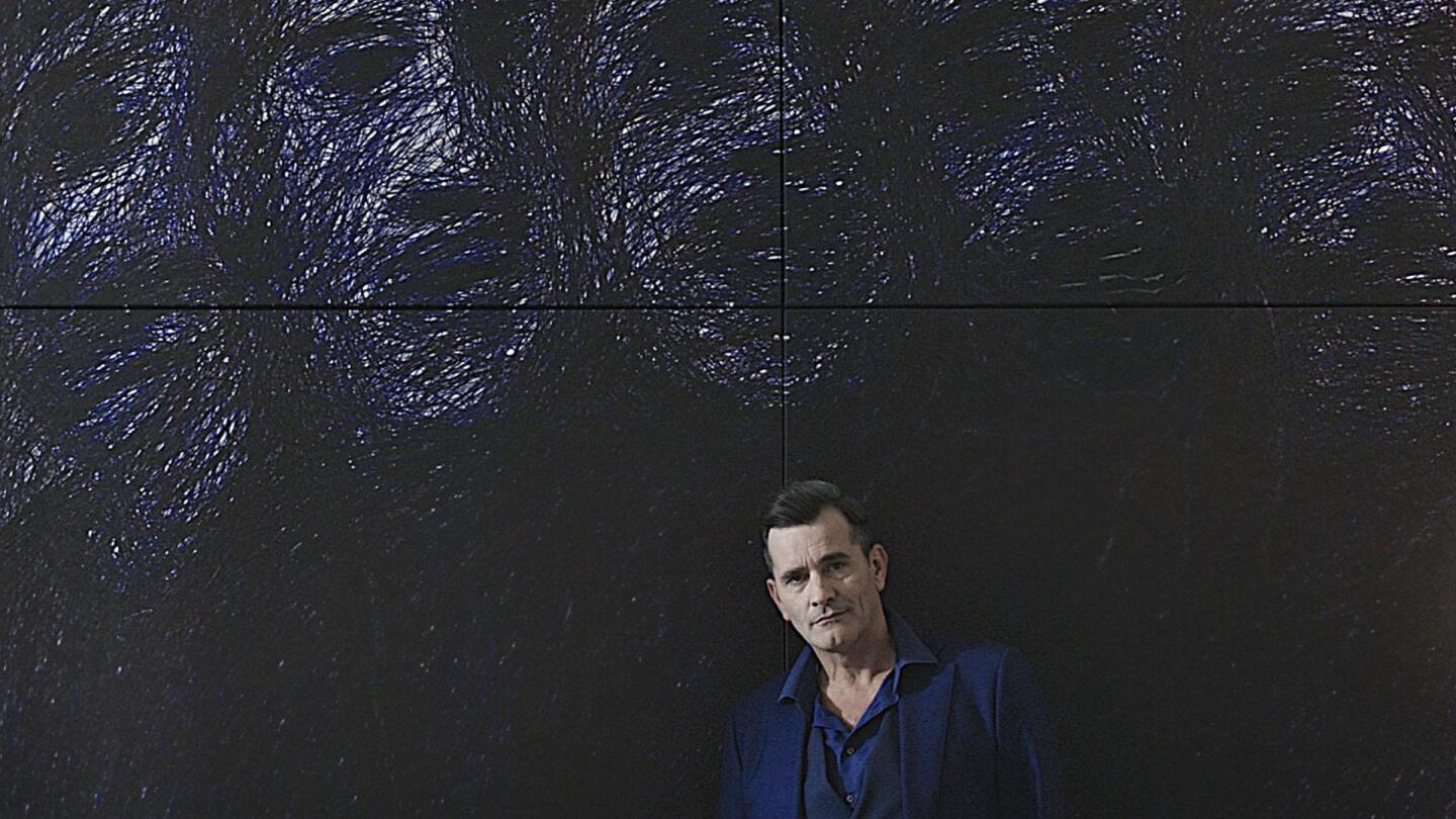 "Professor T (Koen De Bouw) standing against a dark wall with impressionistic images of faces on it. | ""Professor T: Season 2 - Diamond"""