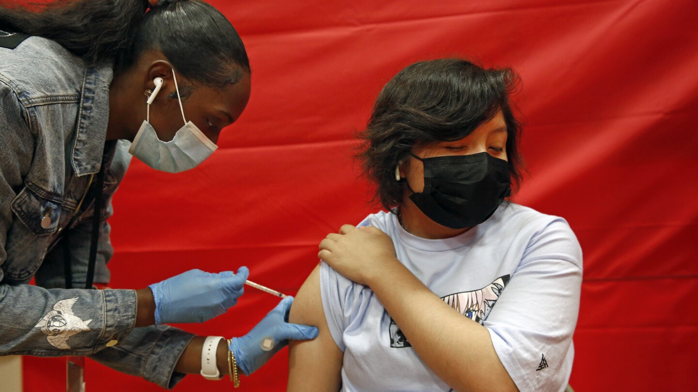 A young man in long black hair gets a vaccine from a young Black woman wearing a ponytail.