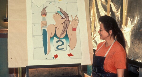 Barbara Carrasco standing next to her print 'Self-Portrait' made in 1984