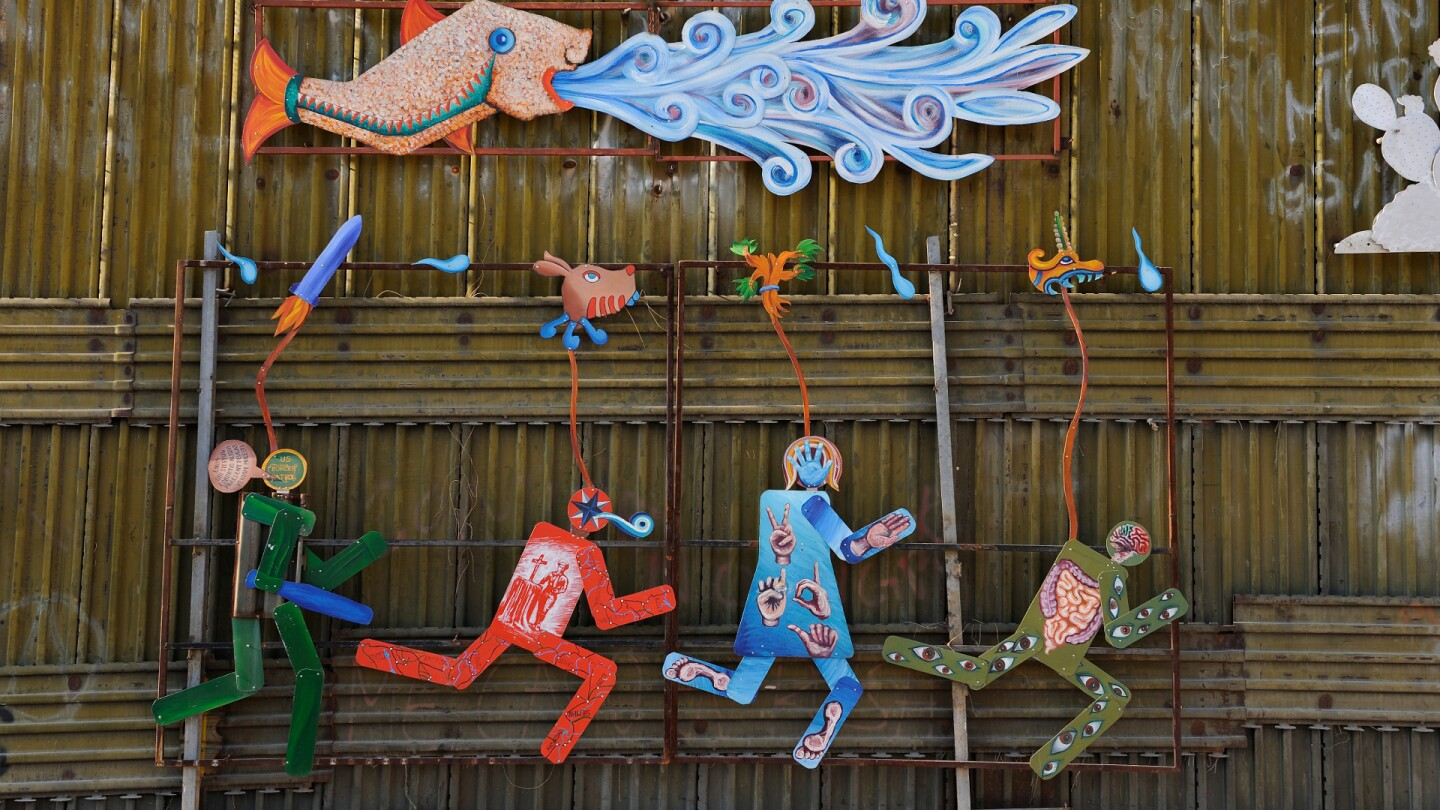 Art on the Mexico/U.S. border fence depicting the struggle between the U.S. Border Patrol and migrants