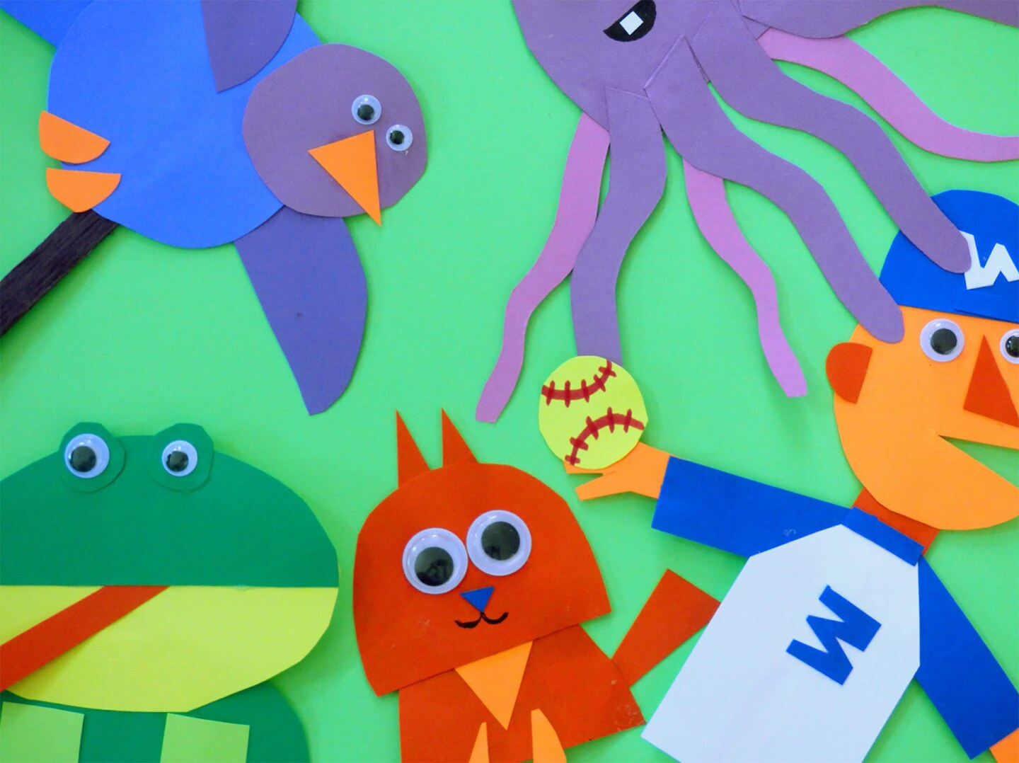 Several puppets of animals (kitty, frog, bird, squid and baseball player) on top of a green background
