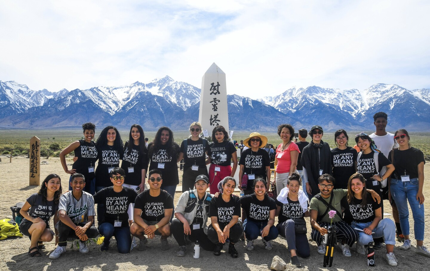 Members of Vigilant Love gather in front of a World War II monument for Manzanar Cemetery.