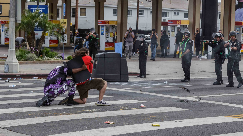 Protestors kneel as police aim at them on May 30, 2020 | Trevor Jackson