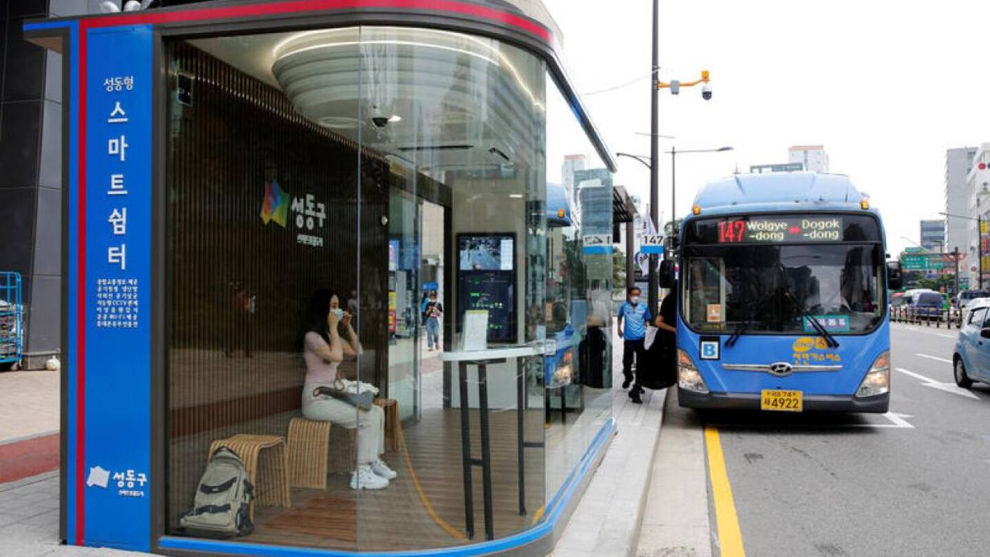 A woman wears a mask inside a glass-covered bus stop in which a thermal imaging camera, UV sterilizer, air conditioner, CCTV and digital signage are set, to avoid the spread of COVID-19 in Seoul, South Korea, August 14, 2020. | REUTERS/Heo Ran