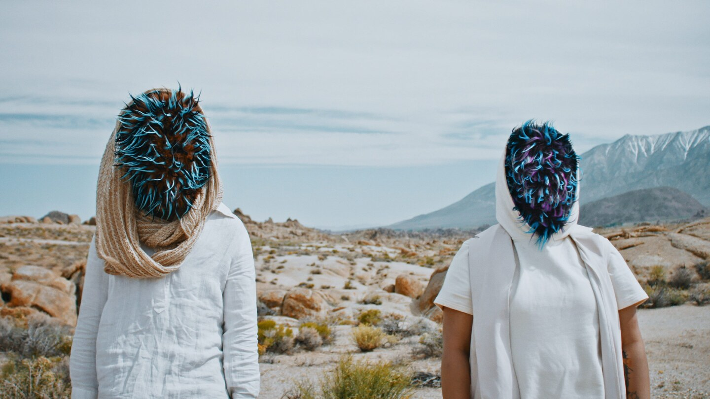 "Still from Bells Atlas' ""Be Brave"" with two people with masks at a coast"