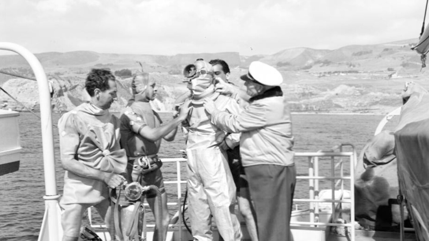 Captain Allan Hancock and three other men assist Jacques Cousteau to suit up for scuba diving (aqua-lung diving) to fish for sharks from the Velero IV, ca. 1950. | Allan Hancock Foundation Collection, USC Libraries
